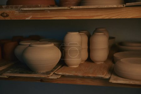 ceramic bowls and dishes on wooden shelves at pottery studio
