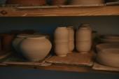 bols en céramique et vaisselle sur des étagères en bois à l'atelier de poterie