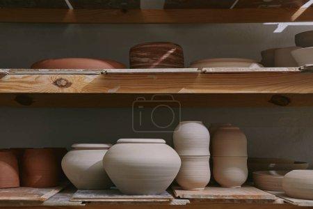 Photo pour Bols en céramique et vaisselle sur des étagères en bois à l'atelier de poterie - image libre de droit