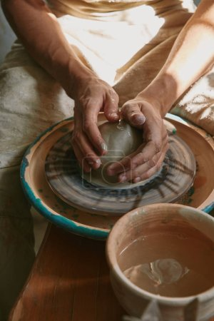 partial view of professional potter working with clay at workshop