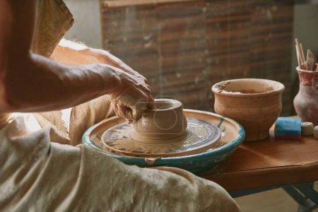 Cropped image de potier professionnel travaillant sur la roue de la poterie à l'atelier