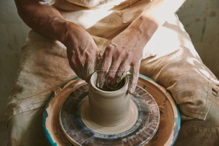 close up view of male potter hands working on pottery wheel at workshop