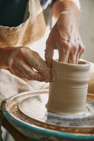 selective focus of man hands working on pottery wheel at workshop