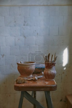 Photo for Selective focus of pottery tools at table in pottery studio - Royalty Free Image