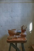 selective focus of pottery tools at table in pottery studio