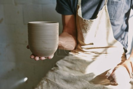 cropped image of professional potter in apron holding clay pot at workshop