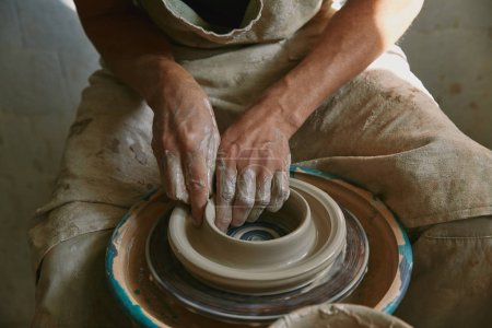 partial view of professional potter working on pottery wheel at workshop