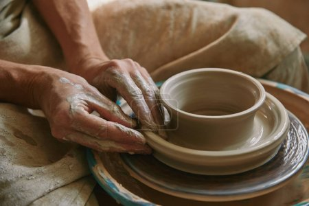 close up view of professional potter working on pottery wheel at workshop
