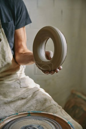 cropped image of professional potter in apron holding clay at pottery studio