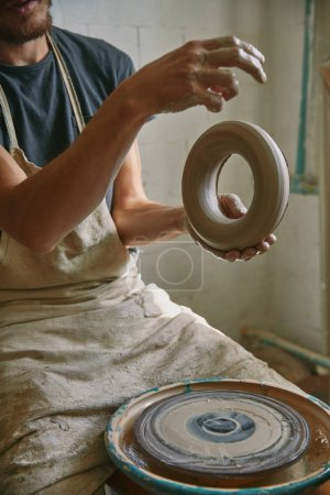 partial view of professional potter in apron holding clay at pottery studio