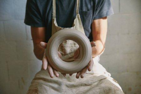 Photo pour Foyer sélectif de potier professionnel dans tablier tenant l'argile au studio de poterie - image libre de droit