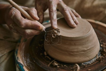 close up view of professional potter decorating clay pot at workshop