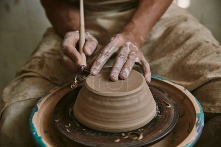cropped image of professional potter decorating clay pot at workshop