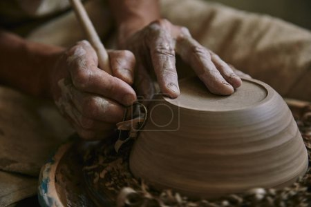Photo for Selective focus of professional potter decorating clay pot at workshop - Royalty Free Image
