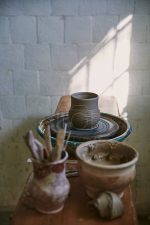 selective focus of clay pot on pottery wheel at workshop