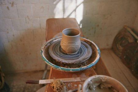 Photo pour Mise au point sélective de pot d'argile sur la roue de la poterie à l'atelier - image libre de droit