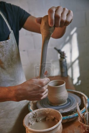 cropped image of professional potter in apron working with clay at pottery studio