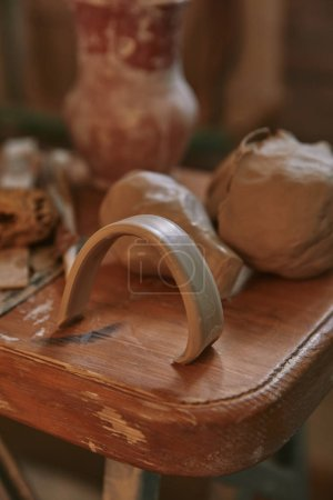 selective focus of clay at wooden table in pottery studio