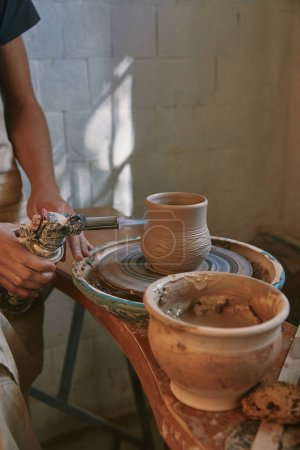 partial view of male potter in apron firing clay pot at pottery studio