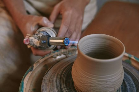 selective focus of male potter firing clay pot at pottery studio