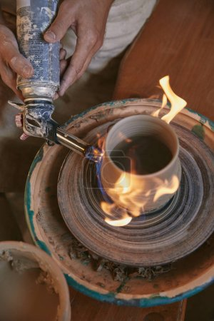 cropped image of male potter firing clay pot at pottery studio