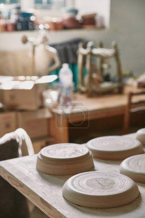 Photo pour Mise au point sélective des plaques à table dans l'atelier de poterie - image libre de droit