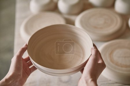 cropped image of woman holding ceramic dish at pottery studio
