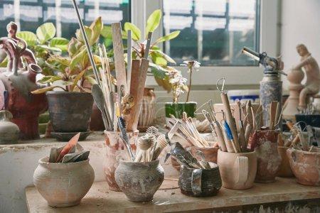 Photo pour Mise au point sélective d'outils de poterie et de pinceaux à table dans l'atelier de poterie - image libre de droit