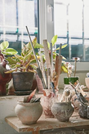 Photo for Selective focus of pottery tools and paintbrushes at table in pottery studio - Royalty Free Image
