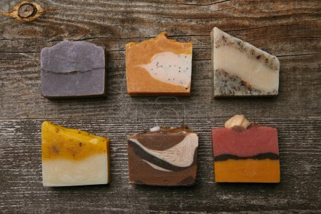 Photo pour Vue de dessus de différentes pièces de savon faites à la main sur plateau en bois rustique - image libre de droit