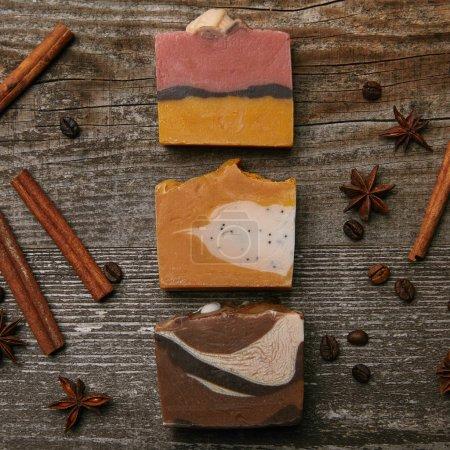 Photo pour Vue de dessus de divers morceaux de savon artisanal avec des épices sur une table en bois rustique - image libre de droit