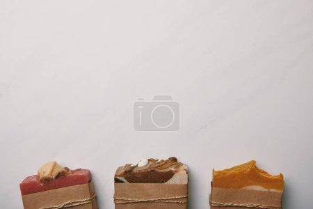 Photo pour Vue de dessus de la rangée de morceaux de savon faits à la main sur la surface de marbre blanc - image libre de droit