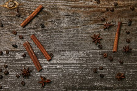 Photo for Top view of cinnamon sticks with anise and coffee beans on rustic wooden table - Royalty Free Image