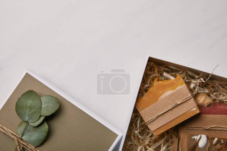 top view of gift box decorated with eucalyptus leaves with soap inside on white marble surface