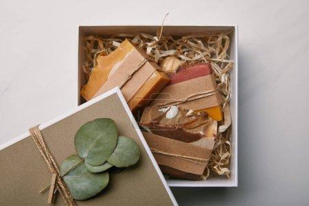 Draufsicht auf Schachtel mit Eukalyptusblättern und Seife auf weißem Marmor