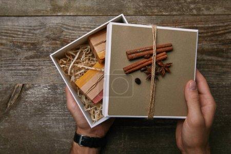 Photo pour Plan recadré de l'homme tenant boîte de savon fait main sur table en bois - image libre de droit
