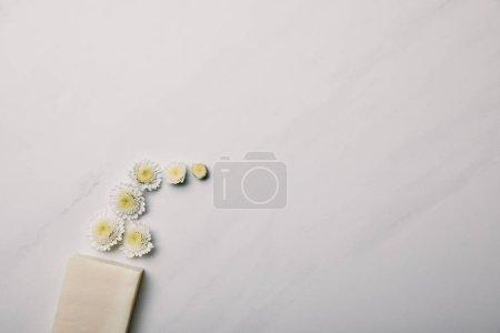 vue de dessus du morceau de savon avec marguerites sur la surface de marbre blanc