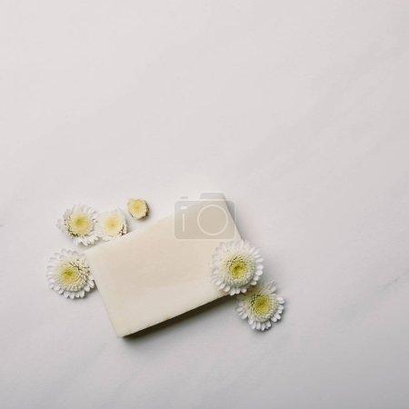 Photo pour Vue de dessus du morceau de savon aromatique blanc avec marguerites sur la surface du marbre blanc - image libre de droit