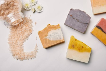 Photo pour Vue de dessus de divers morceaux de savon avec du sel de mer et des fleurs sur la surface du marbre blanc - image libre de droit