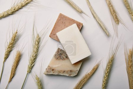top view of various handmade soap with wheat on white marble surface