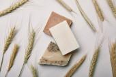 """Постер, картина, фотообои """"вид сверху различных мыло ручной работы с пшеницей на белой поверхности мрамора"""""""