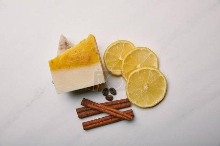 Photo pour Vue de dessus du savon artisanal avec tranches de citron, la cannelle et café sur la surface du marbre blanc - image libre de droit