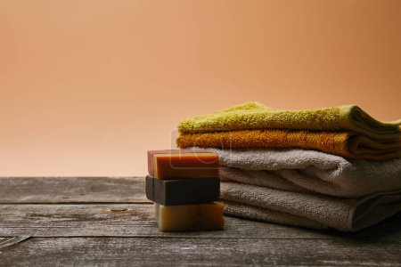 close-up shot of soap pieces with stacked towels on rustic wooden tabletop