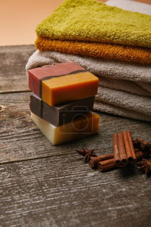 close-up shot of soap pieces with stacked towels and spices on rustic wooden tabletop