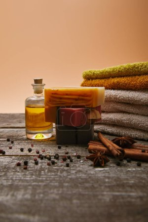 Photo for Close-up shot of soap pieces with stacked towels, spices and massage oil on rustic wooden tabletop - Royalty Free Image