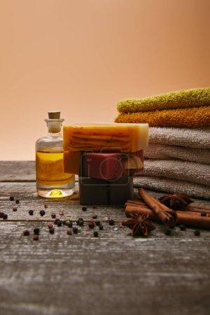 Foto de Primer disparo de piezas de jabón con toallas apiladas, especias y aceite de masaje en el tablero de madera de estilo rústico - Imagen libre de derechos