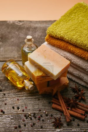 close-up shot of aromatic soap pieces with stacked towels, spices and massage oil on rustic wooden tabletop