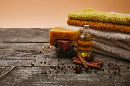 close-up shot of handmade aromatic soap pieces with stacked towels, spices and massage oil on rustic wooden tabletop