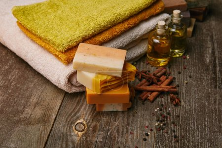 Photo for Close-up shot of handmade soap pieces with stacked towels, spices and massage oil on rustic wooden tabletop - Royalty Free Image