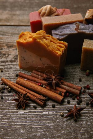 Photo for Close-up shot of homemade soap with cinnamon sticks, anise and coffee on rustic wooden tabletop - Royalty Free Image